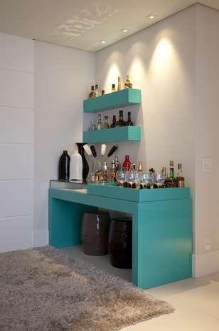 O canto do bar não passa desapercebido com essa cor turquesa linda e tão atual. Note que as garrafas ficam em caixinhas presas à parede. A proposta é da designer Maximira Durigan.