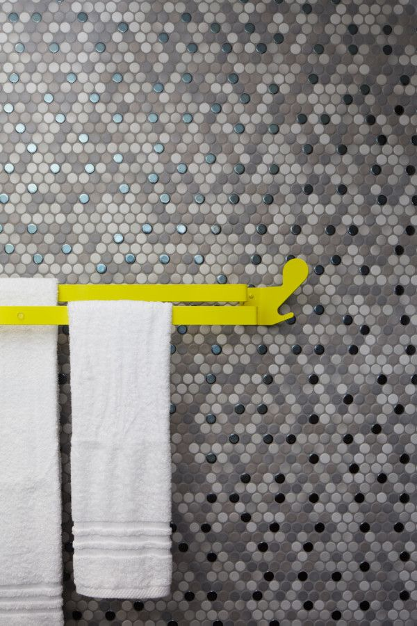 Multi tonal grey & silver spot tiles with contrasting canary yellow towel rail