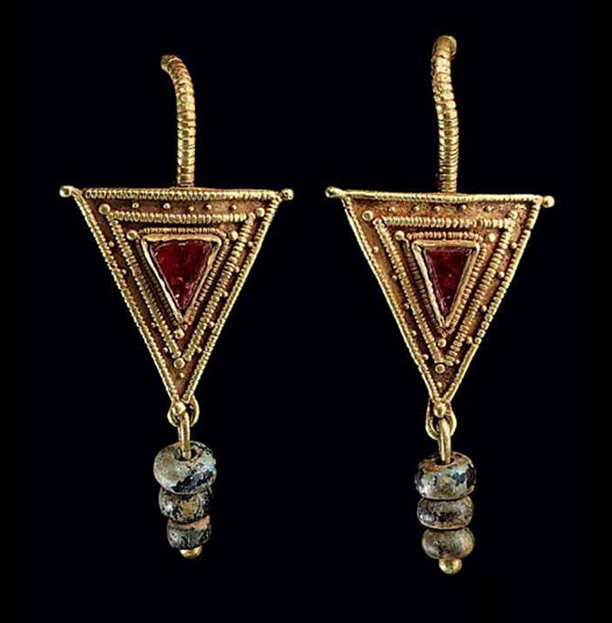 A PAIR OF ROMAN GOLD, GARNET AND GLASS EARRINGS   CIRCA 2ND-3RD CENTURY A.D.   Each with a hooked earwire beaded along its length and tapering to a point, joined to a sheet triangle with a beaded wire fringe, a triangular garnet bezel-set in the center and framed by beaded wire and granulation, a loop at the base joined to a length of wire threaded with three blue glass beads