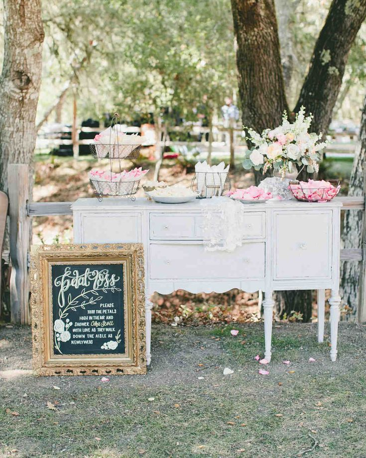 Trending Now: Wedding Ceremony Petal Bars | Martha Stewart Weddings - If you love the idea of everyone choosing which petals they toss, set up baskets of different varities of blooms on a table or vintage dresser, seen here, and provide bags or cones for guests to fill. Your photos will be colorful and lively, and you'll never forget exiting in a shower of unexpected flowers.