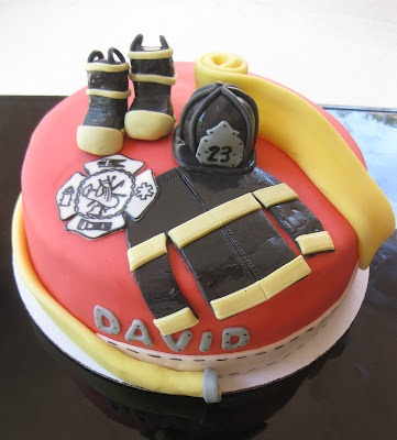 Firefighter cake with hose, turnouts, helmet, boots, and symbol by The Cake Baketress