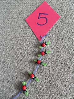 "Simple numbered kite with string for the correct number of pegs to be attached ("",)"