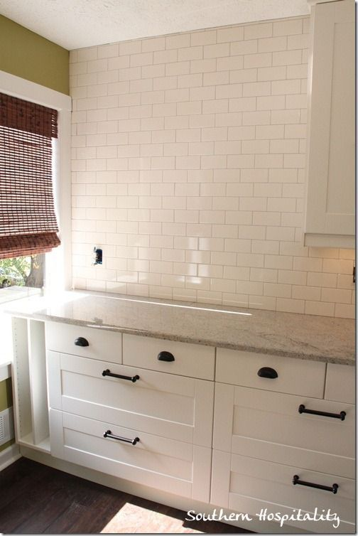 light counter tops, white cabinets, dark hardware, and white subway tile