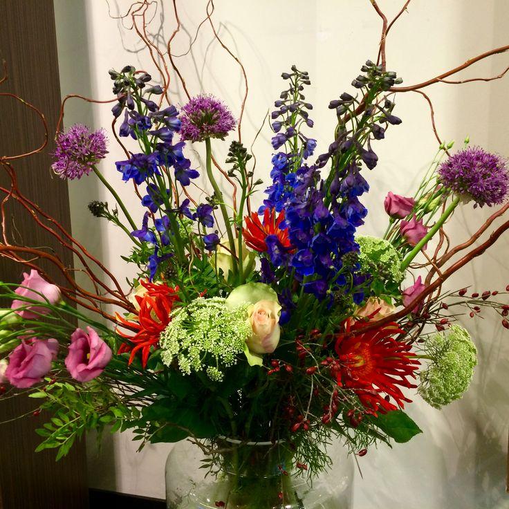 Boeket met kronkelwilg, roze lisianthus, paarse allium, blauwe delphinium, rode gerbera's, rozen en fluitekruid