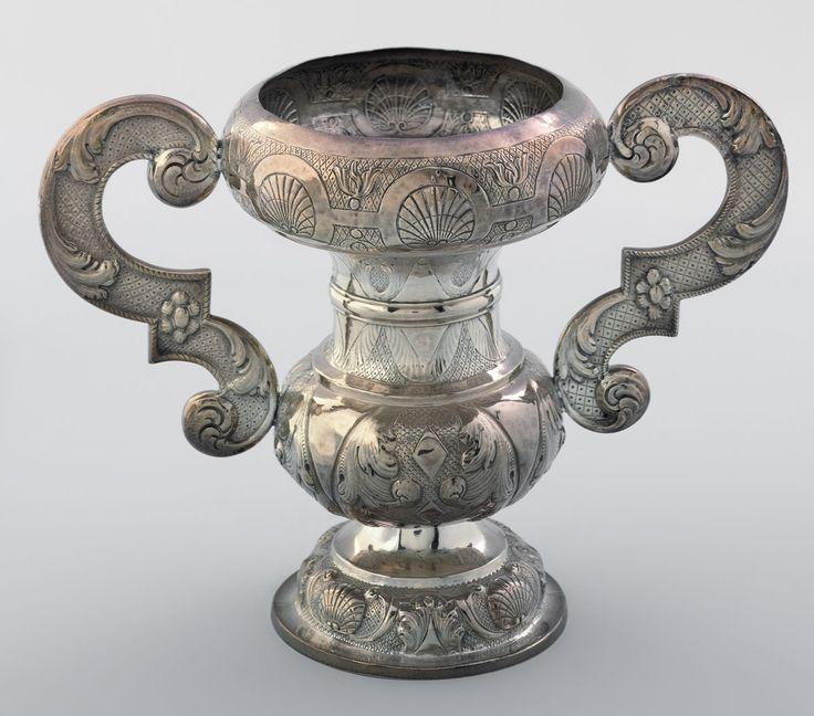 Zilveren vaas, kerkzilver voor op het altaar.     Uit meerdere delen samengestelde, geoorde bloemenvaas. Versieringen in Lodewijk XVI-stijl.