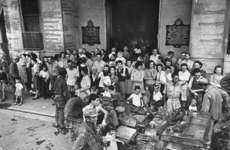 Carl Mydans. Freed American and Filipino prisoners outside main entrance of Santo Tomas University which was used as a Japanese prison camp before Allied liberation forces entered the city. Manila, Luzon, Philippines. February 05, 1945