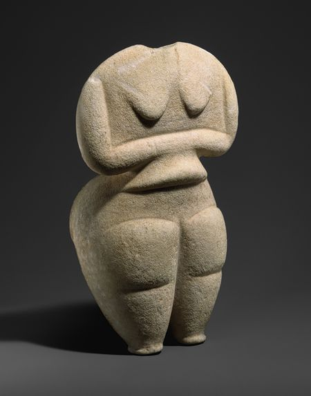 """ca. 4500–4000 BCE. Cycladic Marble Female Figure, a rare type known as""""Steatopygous."""" now missing its head. The crossed arms and relatively thin upper body and stylized simple forms are familiar from the more common cycladic figures made much LATER. But a rounded figure with large hanging breasts, fleshy upper arms and roll on her abdomen, massive buttocks and thighs that taper to tiny stump feet is a rare type indicative of nourishment and fertility. MET"""