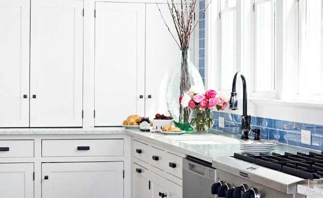 Kitchen- Crisp white cabinetry in the kitchen keeps clutter to a minimum. To bring a pop of color into the room, the seaside palette is reflected with counters made of recycled glass and cement and a vibrant glass subway tile backsplash.