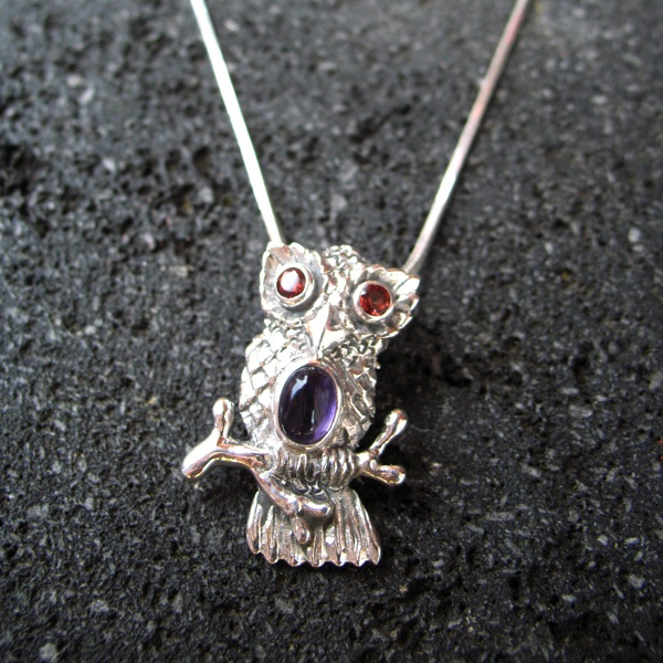 This wise owl set with garnets and amethyst stones winks radiantly from his perch on a sterling silver chain.  A delightful  gift.