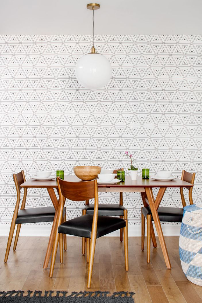 To outfit simple midcentury modern walnut dining table and leather dining chairs, Megan added in geometric removable wallpaper, sourced through Etsy.