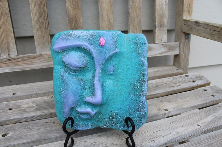 Set this piece in any room to add tranquility and peace!   This Buddha head will inspire peace of mind and will add a pop of color to any corner. Or maybe you have a Yoga studio or meditation room that it may displayed in. This one of a kind Buddha head was made to resemble stone. I personally mixed frit (crushed glass) and layered the colors in a specific order in my mold. Some of the glass had a reaction with one another and became even more stone looking in place. I also added a piece of…
