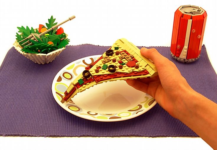 A food creation with zero calories and packed with lots of creativity. Lego pizza sculpture with lego salad and soda.