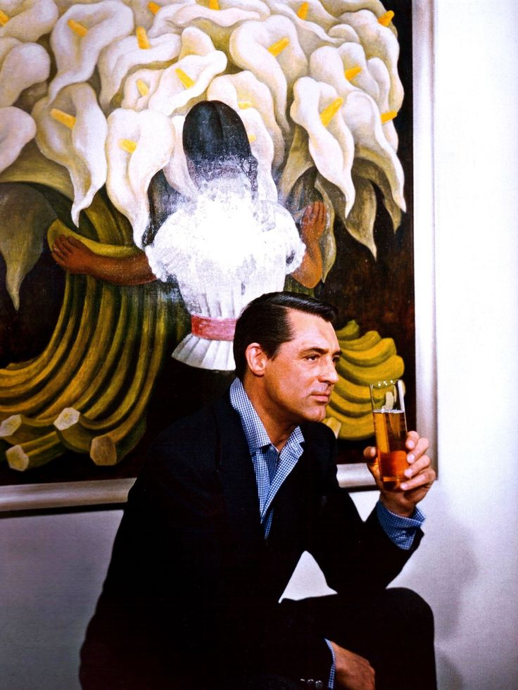 Cary Grant drinking a beer in front of the painting Flower Vendor by Diego Rivera (1955)
