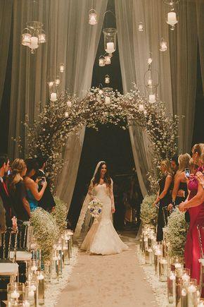 Entrada da cerimônia de casamento com arco de flores e velas