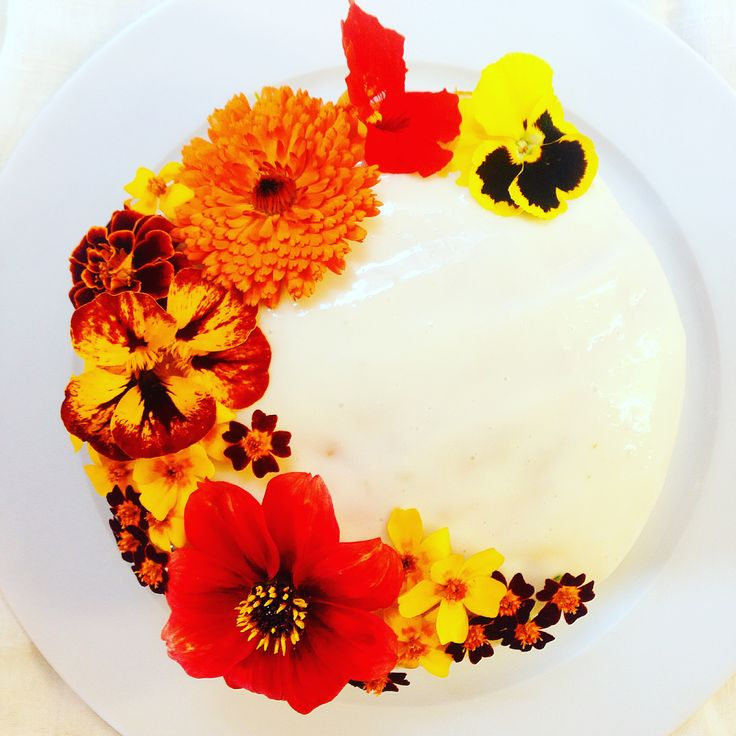 cake with cream cheese frosting and crescent of edible flowers