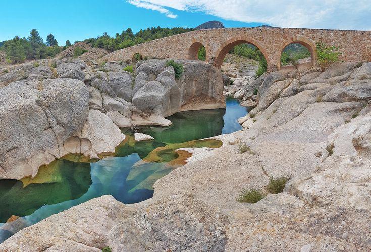 """Nuestra motera recorre tres espectaculares rutas que terminan en Alcañiz. Un lugar mítico en donde su padre, el laureado piloto Jaime Sornosa """"Correcaminos"""", se consagró como Campeón de España de Velocidad en Turismos en el 86. Paisajes definidos por el agua y la influencia musulmana y los frutales que nos conducen hasta las sorprendentes Bóbedas del Frío. Aqui se puede ver el puente de Cananillas en Aguaviva donde está la Casa Rural"""