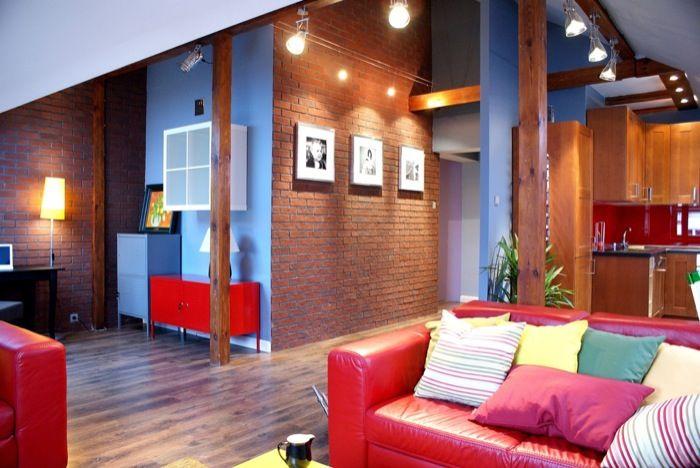 Salon projekt #4735. Nowoczesne wnętrze, łączące nowoczesność z naturą. Drewniane belki nadają pomieszczeniu rustykalny klimat , zaś niebieskie ściany i czerwona kanapa energetycznie ożywiają.