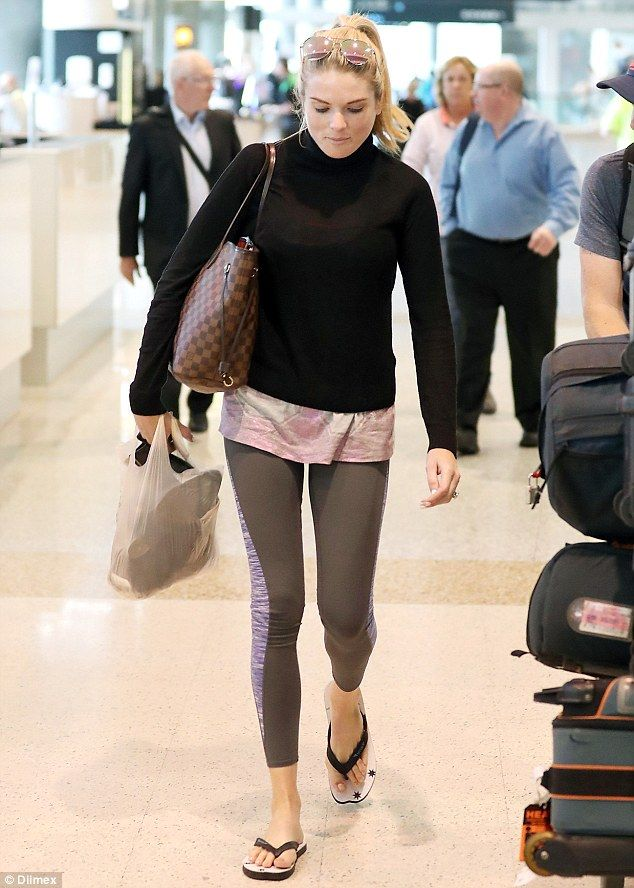 Low-key arrival:Erin Molan flashed her reported '$100,000' engagement ring while wearing mismatched gym leggings and thongs while touching down in Sydney on Monday