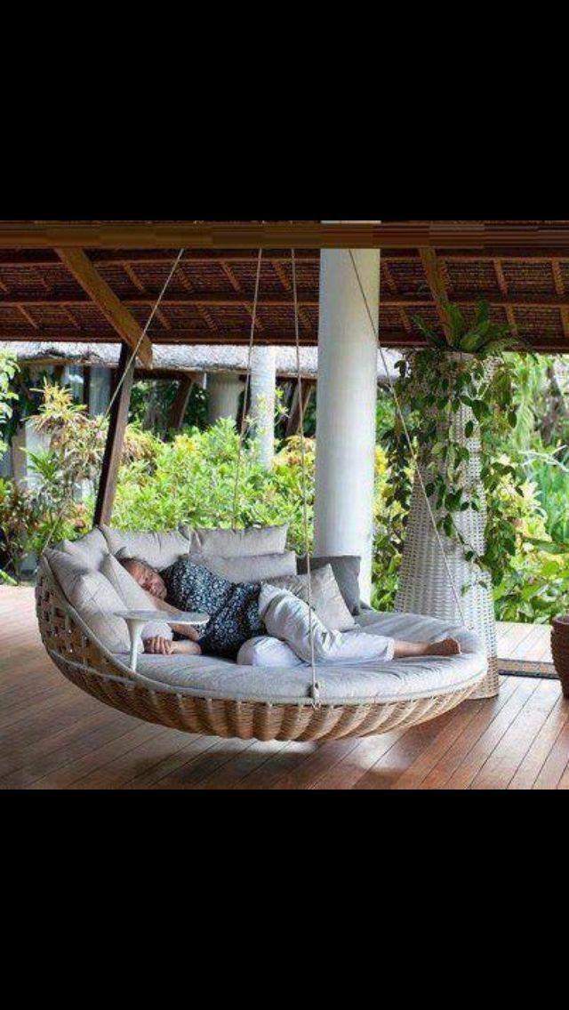 Závěsná houpací ratanová pohovka na verandě -