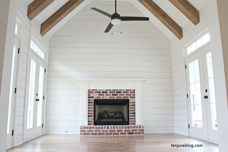 Ten June: The Farmhouse: A Tour of the Living + Keeping Room  rustic brick Craftsman style fireplace, white shiplap walls, vaulted ceiling with rustic wood beams (Minwax stain) and light wooden floors, modern iron ceiling fan, three sets of French doors onto patio