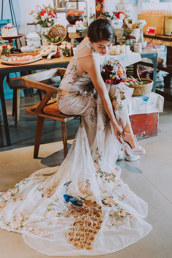 Nyonya bride in a bold embroidered peacock Peranakan Cinobi wedding dress, shoes from Celest Thoi and bouquet from The Vow Florals // Our Baba and Nyonya bridal shower styled shoot is as colourful and delightful as the sarong kebayas and desserts it showcases. Planned and styled by Moments at The Tranquerah in Kuala Lumpur, this blend of traditional Peranakan aesthetics and modern styling is sure to inspire you to embrace a history and culture that is uniquely South East Asian.