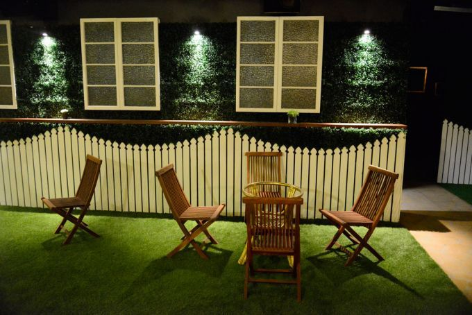 Capulet 188 Brunswick Street, Fort. Valley.   Outdoor furniture on astro turf next to picket fence and window inside Capulet Bar