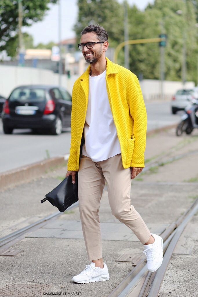 Shop this look on Lookastic:  https://lookastic.com/men/looks/barn-jacket-crew-neck-t-shirt-chinos-athletic-shoes-zip-pouch/11811  — White Crew-neck T-shirt  — Yellow Quilted Barn Jacket  — Black Leather Zip Pouch  — Beige Chinos  — White Athletic Shoes