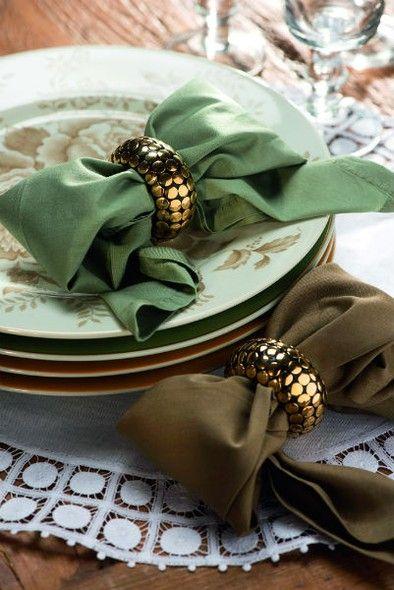 Um anel de guardanapo prende o laço. Guardanapos Roupa de Mesa, pratos e copos D. Filipa, anéis e jogo americano Tania Bulhões