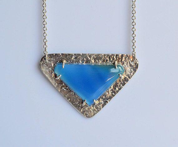 La geometria nei gioielli è una mia passione...e in questa collana si può vedere! Una bellissima agata blu fissato da 6 griffe ad una base dalla texture astratta. La collana è in argento 925 e realizzata a mano.  Ottimo per se stessi o per una persona cara, per donare un tocco minimal e chic. Pezzo Unico, solo tu avrai questo bellissimo ciondolo.  --- Dettagli --- Argento 925 e agata blu Dimensione ciondolo : 5,5x 3,5 cm (2.16x1,37) circa Dimensione pietra: 3,8 x 2,5 cm (1.5x1) Chiusura…