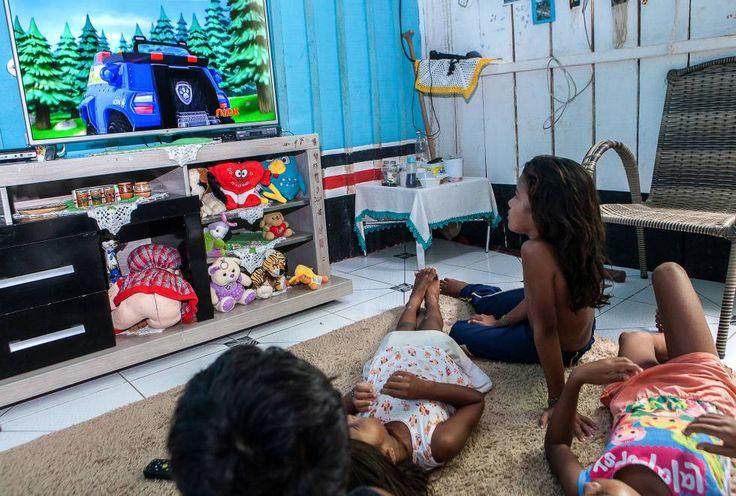 2   ELIANE BRUM (03.04.2017)   A TV, que antes era um lazer acessório, tornou-se o centro da infância de meninos e meninas indígenas que vivem na floresta amazônica, à beira do Xingu. A fotografia deste momento, a que conta da vida como a vida é, hoje, para as crianças da Aldeia Muratu, é esta. Em foto de 24 de março de 2017, Alice (sentada) assiste a desenhos na TV.