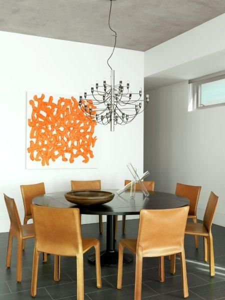 A Flos 2097/30 by Gino Sarfatti hangs over a Zanotta QUADRITONDO Dining Table, surrounded by Cassina CAB Chairs by Mario Bellini in a modern St. Louis Central West End high-rise.