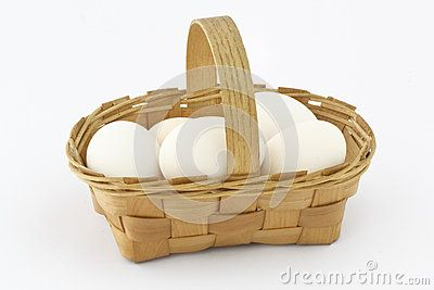 Wooden basket with eggs on white