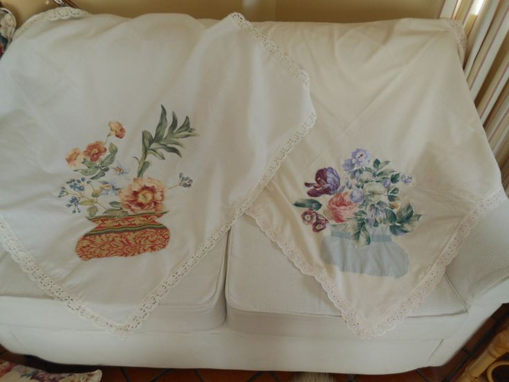Square tablecloths suitable as an overlay on a small round table. Machine applique used to attach flowers arranged in a vase. Edged with lace.