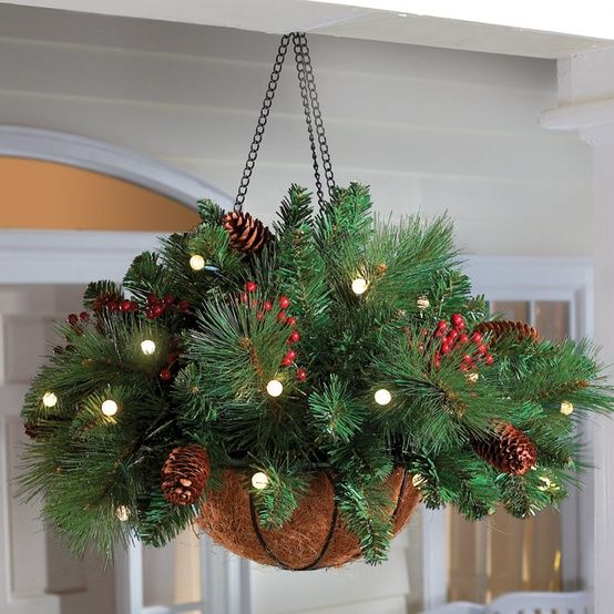Grab hanging baskets now on summer clearance sales! Add a few springs of garland, some battery operated lights, and add some pine cones and holly for this wonderful porch decoration.