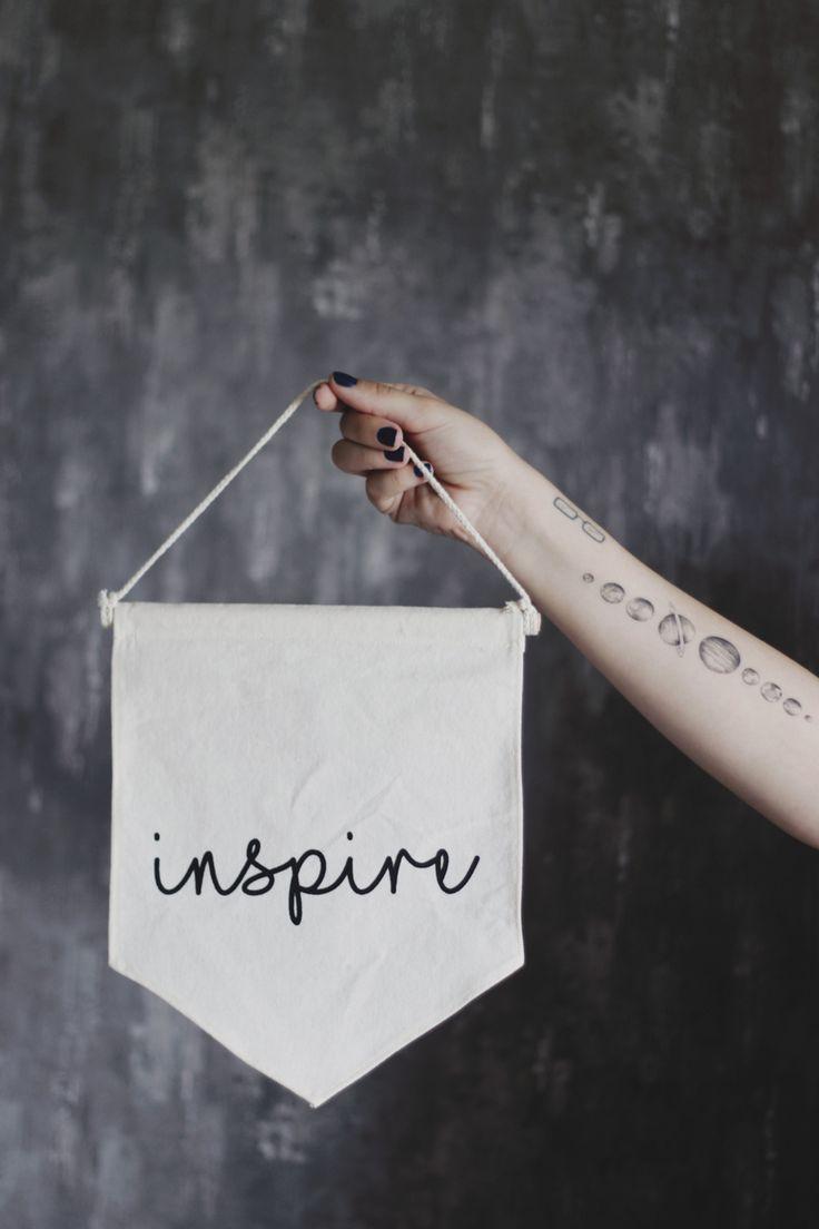 """A diferença entre se inspirar e copiar e a importância de dar créditos.  Foto de Melina Souza segurando uma flâmula com a palavra """"inspire"""".  Tatuagens de planetas no braço.  #melinasouza #tattoo #ink"""