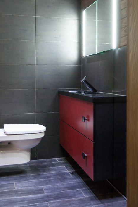 Tämän miehekkään wc:n allaskaapissa on punaiset laminaattiovet sekä päällä musta Talia-allastaso. Hana on Gustavsbergin moderni ja erilainen Coloric-malli.