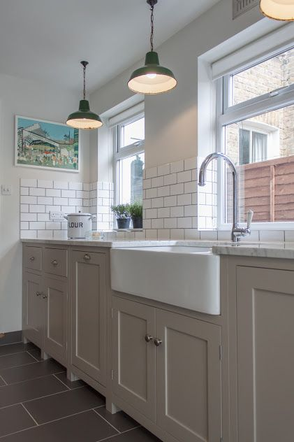 The Hither Green Shaker Kitchen by deVOL - A beautiful example of how to do a galley style Shaker kitchen. A run of cabinets in 'Mushroom' ends with French doors allowing light to stream through, with Carrara Marble worktops lit by salvaged industrial lights making for an eclectic Shaker style.