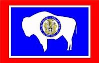 The Wyoming State Flag, designed by Mrs. A.C. Keyes of Casper, was adopted by the fourteenth legislature on January 31, 1917.  The Great Seal of Wyoming is the heart of the flag. On the bison, once the monarch of the plains, is the seal representing the custom of branding. The red border represents the Indian. White is the emblem of purity and uprightness over Wyoming. Blue, the color of the sky and mountains, is symbolic of fidelity, justice and virility.