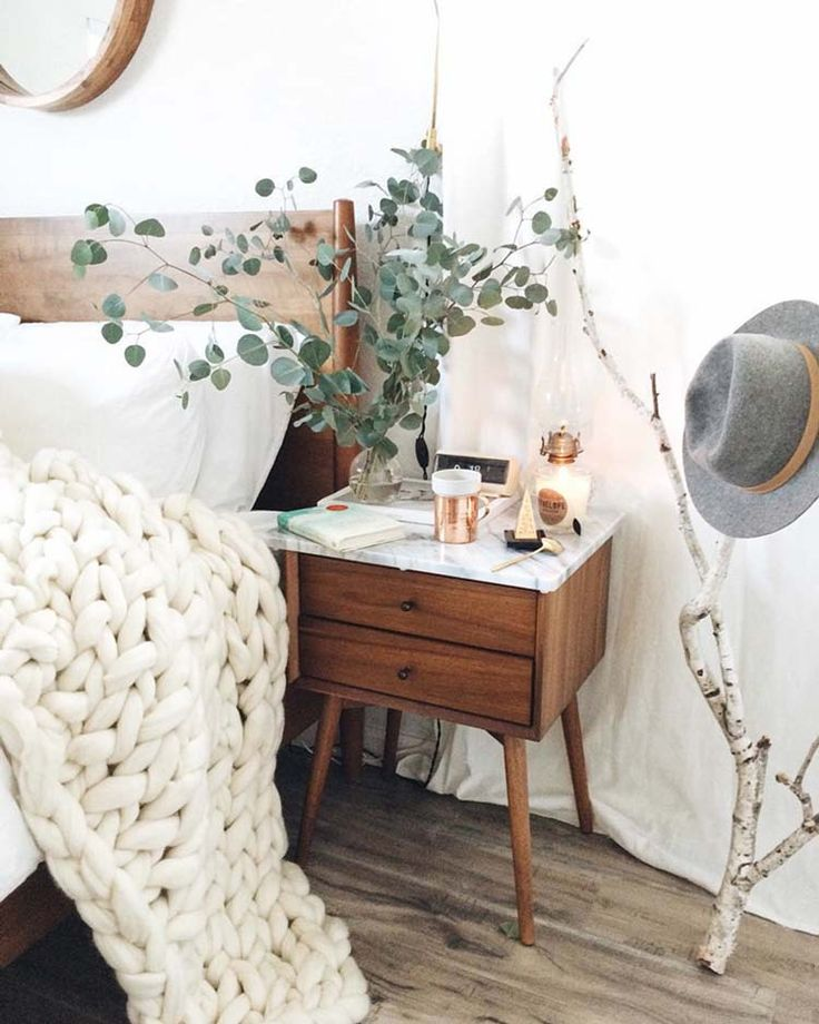 cozy bedroom with mid-century side table, eucalyptus and knit throw