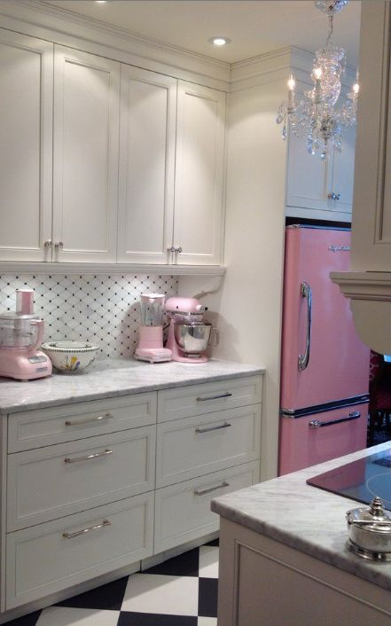 Pink Lemonade Retro Fridge in a beautiful kitchen with crystal chandeliers, marble countertops, large corbel details, and a bold black and white floor. Click to add the Big Chill look to your kitchen. #RetroCool