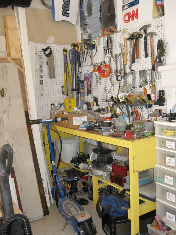 disorganized garage with pegboard and yellow working bench.