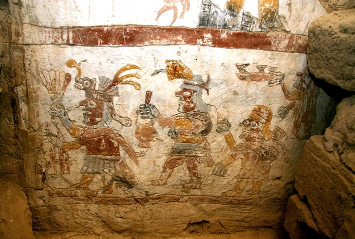 Figures dressed in elaborate garments and headdresses process from right to left across the face of one of the pillars of the Temple of the Painted Pillars at the site of Pañamarca in northwest Peru. The figures hold typical Moche objects, including a plate with three purple goblets, a multicolored stirrup-spout bottle, and a feather fan.