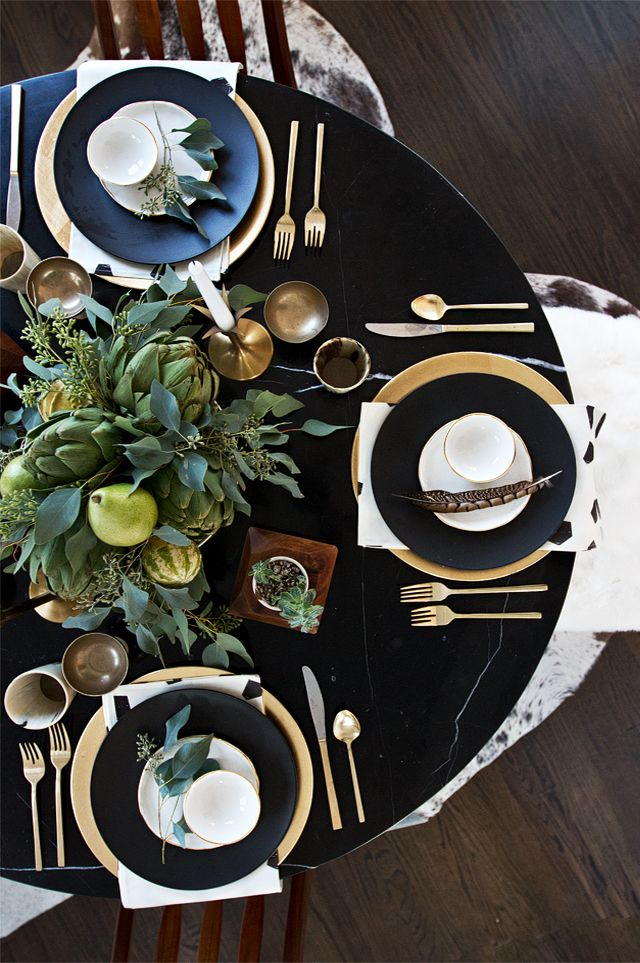 An elegant black and gold Thanksgiving tablescape with feathery touches