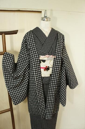 黒の地に、またたく星のような白の十字が織り出されたモダンメルヘンウールのアンサンブル(羽織と着物のセット)です。