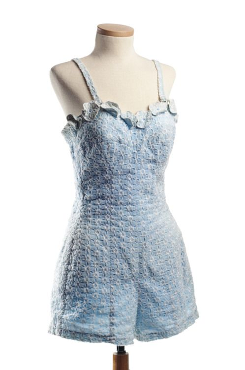 Woman's blue cotton and white eyelet bathing suit, 1959. This De Weese Design suit and matching cover-up were part of the donor's trousseau. The suit has a back zipper and elastic smocking for fit.