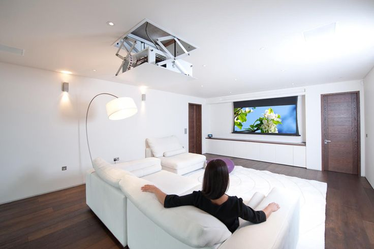 Concealed projector drops from ceiling and projection screen descends in front of flat-panel TV in this sleek modern media room