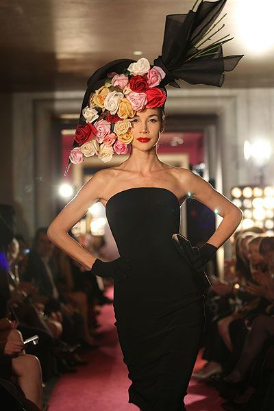 Philip Treacy for McQueen this headpiece resembles a flower bouquet, the flowers mould around the models head, this frames the face. the flowers look quite large and have a red/pink/yellow/white colour palette.