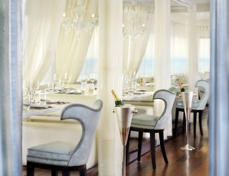 Thomas wanted to bring a beach vibe to the Penthouse Restaurant, even though it is up on the 18th floor.  White upholstery and sheer white curtains reflect the sun and sand atmosphere while specific touches like dolphin-shaped chair backs and a seashell-imprinted bar reference the sea. The plank hardwood floors give the feeling of a boardwalk while curtained cabanas serve as banquettes, though each has a Murano white chandelier for a touch of elegance.