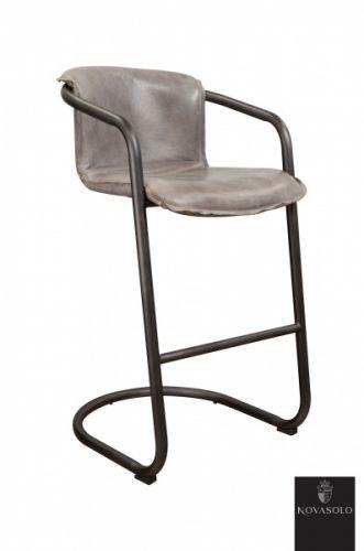 """Råtøff Old Amsterdam smokey grey barstol med historisk preg! Stolen er produsert av """"vintage skinn"""" og har et rammeverk i pulverlakkert jern.     Stolen har en karakterisk """"smokey grey"""" farge. Dette innebærer at det underliggende skinnet er farget brunt og at det deretter er påført en grå avsluttende patina. Vi gjør oppmerksomme på at fargevariasjoner vil forekomme innad hver enkelt stol og fra stol til stol og at dette er en naturlig og bevisst del av produktet."""