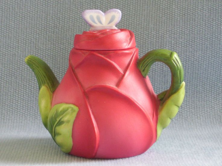 "Avon Season's Treasures Miniature Teapot Collection ""Rose"" teapot, in shape of red and pink flower nestled in green leaves, with blue butterfly as knob, 3"" high, 1995, porcelain"
